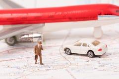 Miniatuurbeeldjes van reiziger met kaart, vliegtuig, auto Stock Foto's