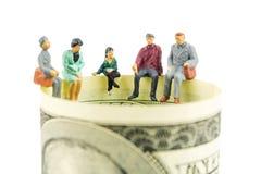 Miniatuurbeeldjesbespreking over de rand van 100 dollarbankbiljet Royalty-vrije Stock Fotografie
