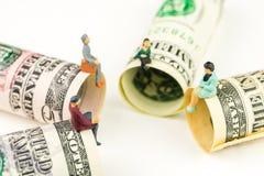 Miniatuurbeeldjesbespreking over de rand van 100 dollarbankbiljet Stock Foto's