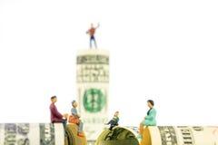 Miniatuurbeeldjesbespreking over de rand van 100 dollarbankbiljet Royalty-vrije Stock Foto
