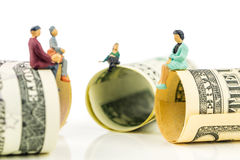 Miniatuurbeeldjesbespreking over de rand van 100 dollarsbankbiljetten Royalty-vrije Stock Fotografie