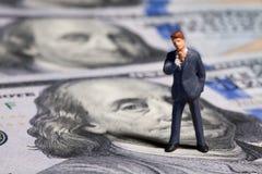 Miniatuurbeeldjezakenman met 100 dollarsbankbiljet op achtergrond Royalty-vrije Stock Afbeelding