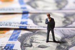 Miniatuurbeeldjezakenman met 100 dollarsbankbiljet op achtergrond Royalty-vrije Stock Fotografie
