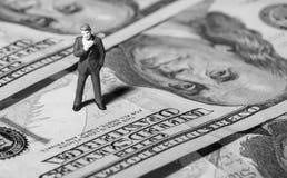 Miniatuurbeeldjezakenman met 100 dollarsbankbiljet op achtergrond Royalty-vrije Stock Foto's