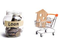 Miniatuurblokhuis en de inschrijving 'Lening ' Het kopen van een huis in schuld Familieinvestering in onroerende goederen en risi royalty-vrije stock fotografie