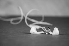 Miniatuurcijfer die aan Muziek luisteren en op Earbuds zitten Royalty-vrije Stock Foto's