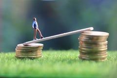 Miniatuurcijfer jonge bussinesman houdt proberend om hoger inkomen lopend te krijgen bij stapel van muntstuk bij vers groen gras  stock foto's
