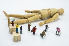 Miniatuurcijfers die houten pop omringen royalty-vrije stock foto's