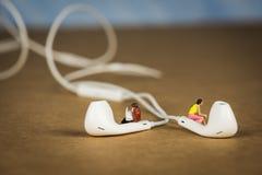 Miniatuurcijfers die op Earbuds zitten die aan Muziek luisteren Royalty-vrije Stock Foto's