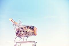 Miniatuurdiesupermarktboodschappenwagentje met gouden muntstukken wordt gevuld Stock Foto