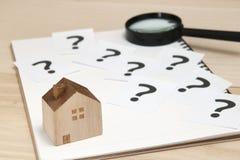 Miniatuurhuis en vele vraagtekens op Witboeken Huis met vraagtekens en vergrootglas Concept 6 van onroerende goederen Stock Fotografie