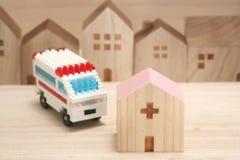 Miniatuurhuizen, het ziekenhuis en ziekenwagen op hout royalty-vrije stock afbeelding