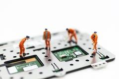 Miniatuurmensen: Arbeiders die kringsraad, elektronikareparatie herstellen Gebruiksbeeld voor steun en onderhoudszaken royalty-vrije stock afbeeldingen