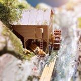 Miniatuurmensen: arbeiders op zaagmolen bij de rivier Macrofoto, ondiepe DOF stock afbeelding