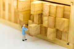 Miniatuurmensen: Arbeidersduw het houten logboek terug in plaats Beeldgebruik voor het toewijzen van ruimte aan voorraad, pakhuis royalty-vrije stock foto