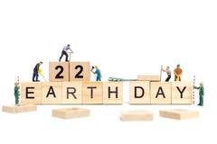 Miniatuurmensen: Arbeidersteam de Aarde van het de bouwwoord ` dag ` op houten blok Royalty-vrije Stock Afbeeldingen