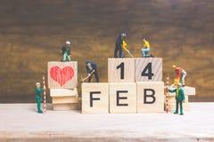 Miniatuurmensen: Arbeidersteam de bouwwoord ` 14 februari ` op houten blok Royalty-vrije Stock Afbeelding