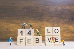Miniatuurmensen: Arbeidersteam de bouwwoord ` 14 februari ` op houten blok Royalty-vrije Stock Fotografie