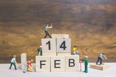 Miniatuurmensen: Arbeidersteam de bouwwoord ` 14 februari ` op houten blok Stock Afbeelding