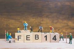 Miniatuurmensen: Arbeidersteam de bouwwoord ` 14 februari ` op houten blok Royalty-vrije Stock Foto