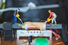 Miniatuurmensen: Arbeidersteam die Elektronische Kringen herstellen stock foto