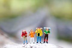 Miniatuurmensen: backpacker het vieren succes die zich op bovenkant bevinden royalty-vrije stock afbeeldingen