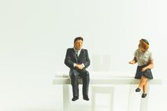 Miniatuurmensen bedrijfsconceptenzitting op stoel met een ruimte stock afbeelding