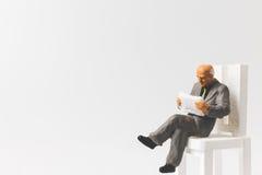 Miniatuurmensen bedrijfsconceptenzitting op stoel met een ruimte stock afbeeldingen