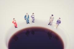 miniatuurmensen commerciële teamzitting op witte havin van de koffiekop Royalty-vrije Stock Foto