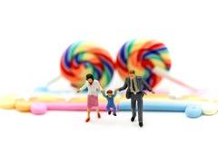 Miniatuurmensen: de hand van de familieholding met Kleurrijk van suikergoed royalty-vrije stock foto