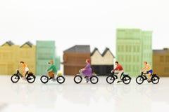 Miniatuurmensen: De mensen gebruiken fietsen als voertuigen om te reizen Beeldgebruik voor energievermindering en oefening binnen royalty-vrije stock fotografie