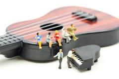 Miniatuurmensen: de minipiano van het mensenspel met het zitten op akoestische gitaar de tijd van ontspant of de muziek ontspant  stock afbeelding