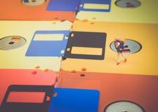 Miniatuurmensen: De reizigers lopen op de oude diskette Stock Foto