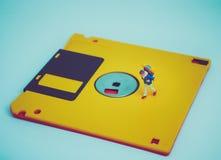 Miniatuurmensen: De reizigers lopen op de oude diskette Royalty-vrije Stock Afbeeldingen