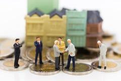 Miniatuurmensen: de zakenlieden maken een overeenkomst Beeldgebruik voor verplichting, overeenkomst, besparing, financiën, geld,  Royalty-vrije Stock Foto's