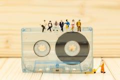 Miniatuurmensen: De zakenman zitten en de lezingskrant op Compacte Cassette Beeldgebruik voor muziek, bedrijfsconcept Royalty-vrije Stock Afbeeldingen