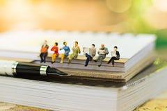 Miniatuurmensen die op boek zitten die als achtergrondonderwijs of bedrijfsconcept gebruiken Stock Foto