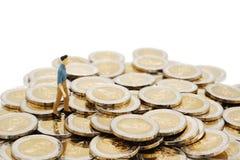 Miniatuurmensen die op stapel van nieuwe 10 Thaise Bahtmuntstukken lopen royalty-vrije stock afbeelding