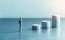 Miniatuurmensen die zich met het kijken bevinden stapelmuntstuk over financia Stock Foto's