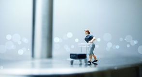 Miniatuurmensen - een vrouw duwt een kar met bagage Royalty-vrije Stock Fotografie