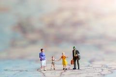 Miniatuurmensen: Familie die hand in hand met op wereldkaart lopen stock foto
