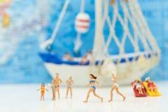 Miniatuurmensen: Families die op het strand gelukkig lopen Heb een boot als achtergrond, als bedrijfsreisconcept dat wordt gebrui stock foto
