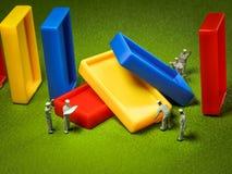 Miniatuurmensen: Geholpen de arbeiders herstellen de instorting van Domino` s blokken Stock Foto's