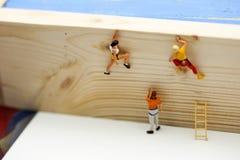 Miniatuurmensen : het beklimmen van ladders om tot de bovenkant van po te krijgen stock fotografie