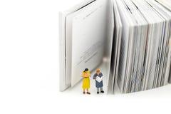 Miniatuurmensen: het lezen van een boek en een Woordenboek die voor conce gebruiken stock fotografie