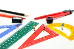 Miniatuurmensen: leraar en student met Groep Onderwijs de hulpmiddelenlevering van kantoorbehoeftenhulpmiddelen terug naar school stock foto