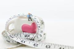 Miniatuurmensen: Mensenzitting op glas met de taille rond en het drinken koffie, koekje Het beeldgebruik voor gezondheidsconcept, stock foto