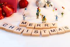 Miniatuurmensen met de ballon van de familieholding met partij op Vrolijke Kerstmis stock afbeelding