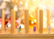 Miniatuurmensen met de ballon van de familieholding met partij op Vrolijke Kerstmis royalty-vrije stock afbeelding