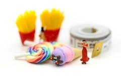 Miniatuurmensen: mooie vrouwenzitting bij het meetlint met royalty-vrije stock foto